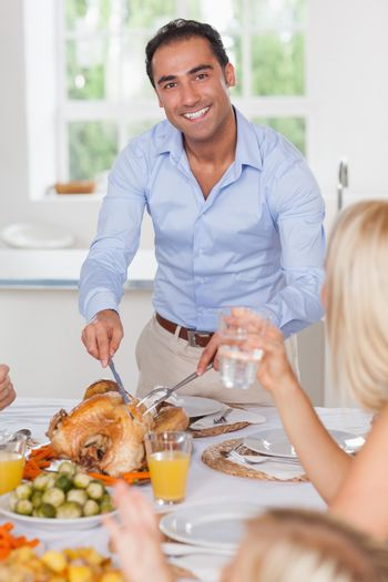 Smiling man carving the turkey