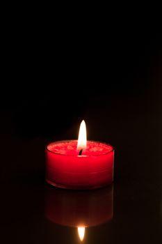 Lit pink tea light candle