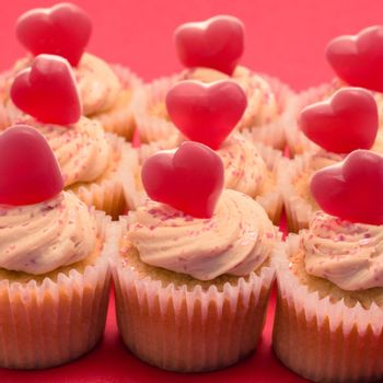 Valentines cupcakes with love hearts on pink background