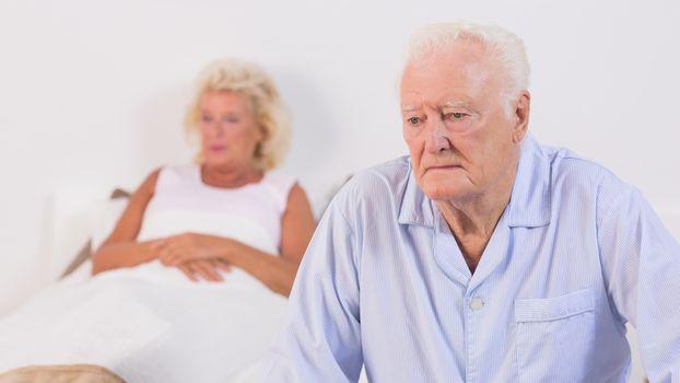 Unsmiling aged couple