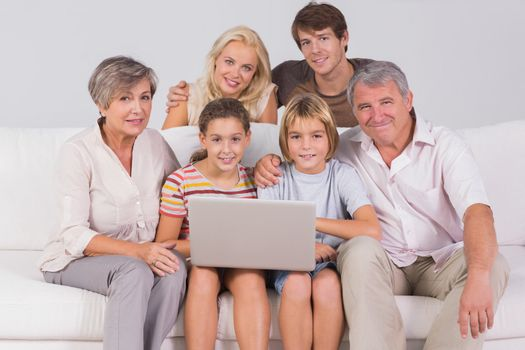 Family portrait looking at camera with a laptop in sitting room