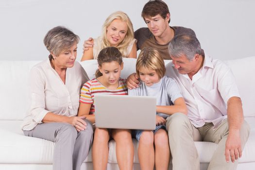 Family looking at laptop on couch in sitting room