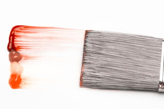 Paintbrush with a red and orange brush stroke