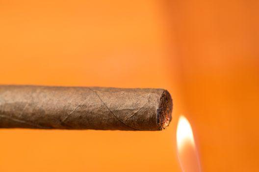 Someone lighting a cigar