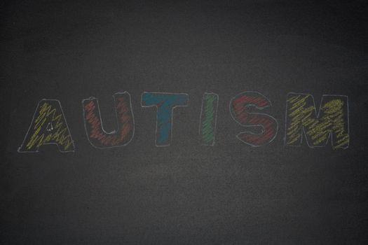 Autism spelled out in chalk and coloured in