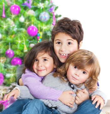 Happy kids near Christmas tree, three little friends enjoying New Year party, Christmastime holidays, best friends, happiness concept