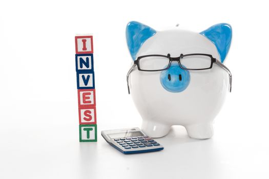 Blue and white piggy bank wearing glasses with invest building blocks