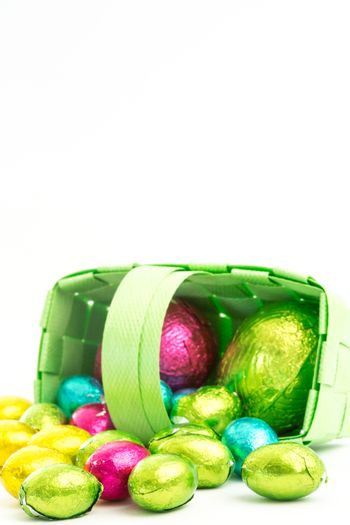 Foil wrapped easter eggs spilling from a basket