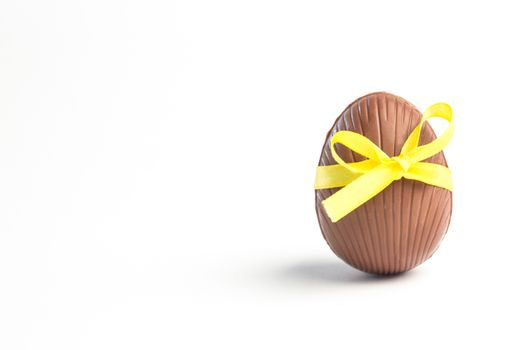 Chocolate easter egg in a yellow ribbon