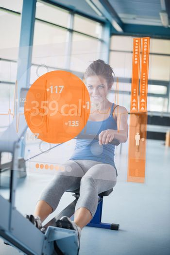 Front view of a girl on rowing machine with futuristic interface showing calories