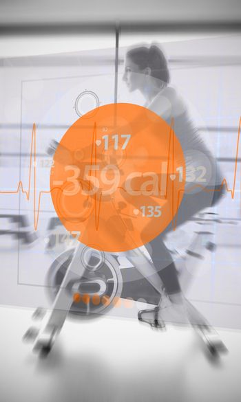 Woman riding exercise bike with futuristic interface showing lost calories