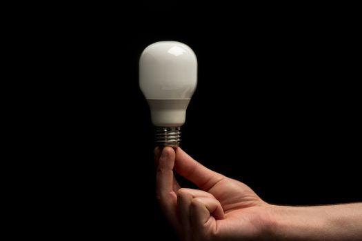 Man holding economic light bulb in his fingertips