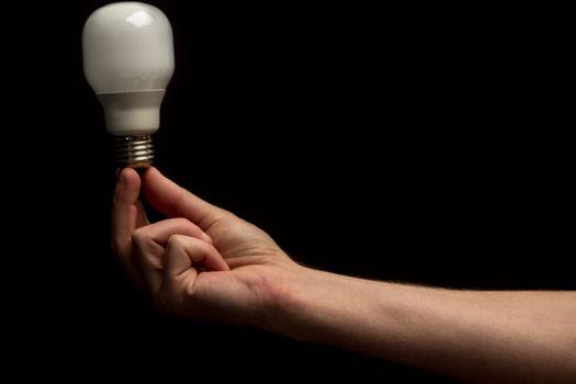 Man holding economic bulb in his fingertips