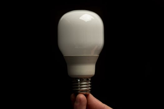 Man holding economic light bulb in his fingertips close up