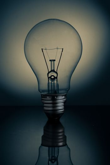 Big clear light bulb standing on reflective surface