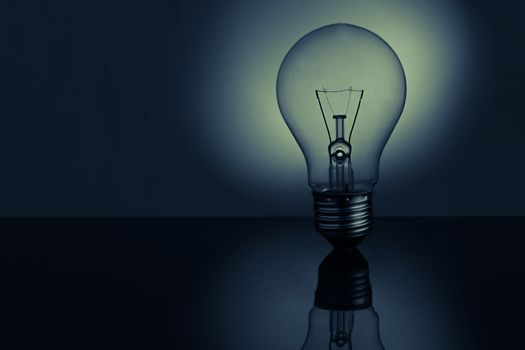 Light bulb standing on bright reflective surface