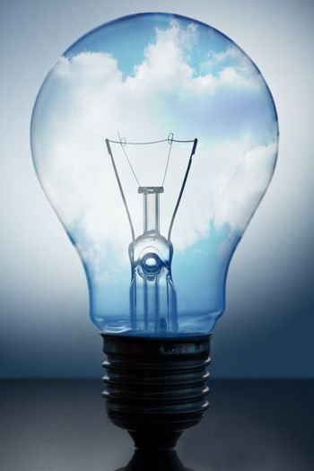 Close up of big light bulb standing with bright blue sky in it