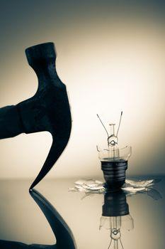 Hammer silhouette beside broken light bulb