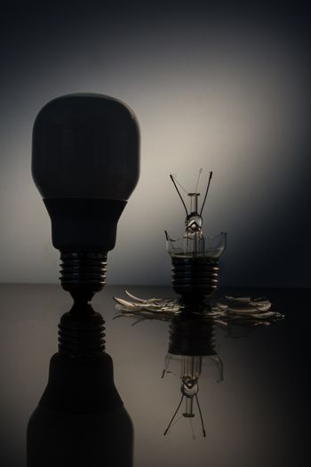 Economic bulb silhouette standing next to a broken clear light bulb