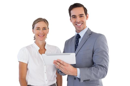 Smiling co workers using a tablet pc