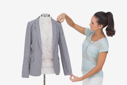 Fashion designer measuring blazer sleeve