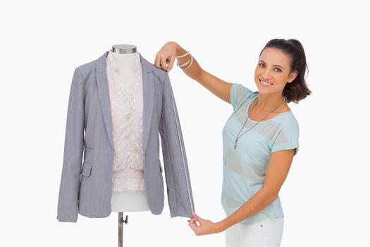 Fashion designer measuring blazer sleeve on mannequin and smilin