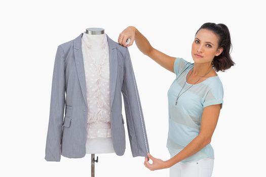 Designer measuring blazer sleeve on mannequin