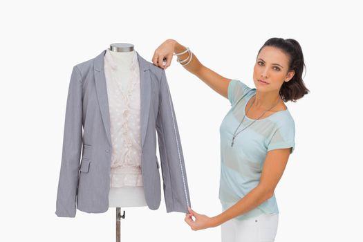 Fashion designer measuring blazer sleeve on mannequin and lookin