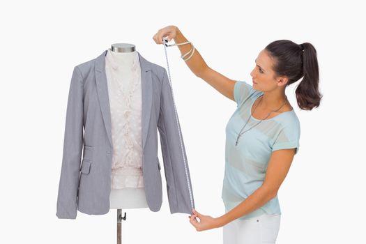 Fashion designer measuring blazer sleeve on mannequin