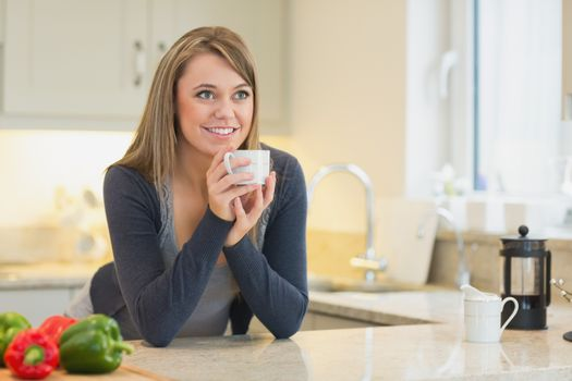 Woman in the kitchen drinking hot beverage
