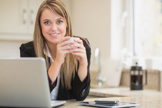 Happy woman holding hot beverage with laptop