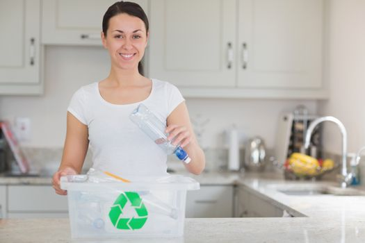 Woman throwing bottle into recycling bin