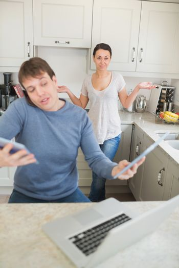 Man busy with technology while his wife wondering why in kitchen
