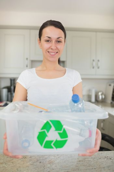 Woman holding full recycling bin