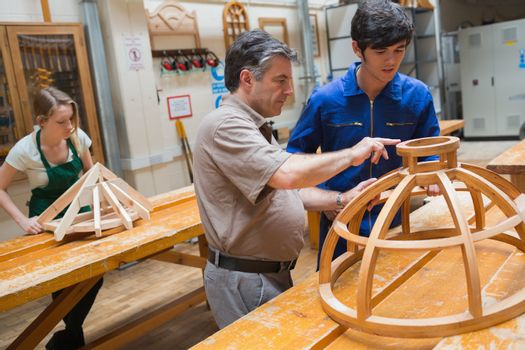 Teacher helping a student in a woodwork class
