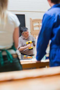 Teacher of a woodworking class explaining