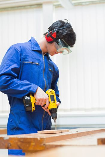 Student of a woodworking class drilling a hole
