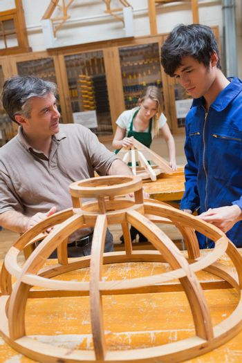 Teacher and a student in a woodworking class working on a frame