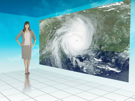 Businesswoman standing next to futuristic screen showing weather on a satellite map