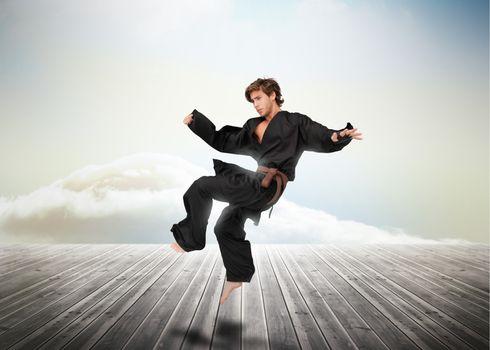 Handsome martial arts fighter over wooden boards