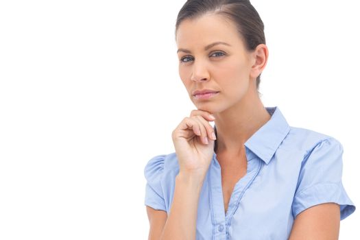 Stern businesswoman with hand on chin