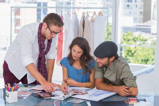 Fashion designers watching fashion photos in magazine