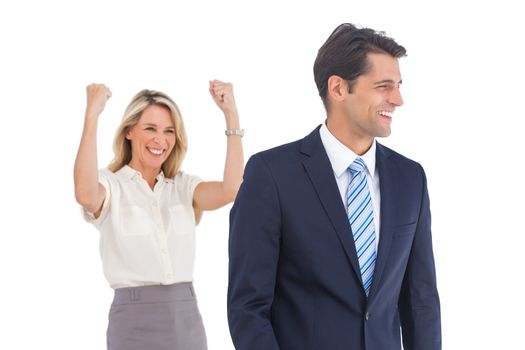 Businesswoman with raised arms and her coworker