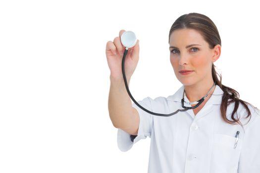 Stern nurse holding up stethoscope
