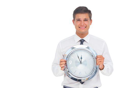 Concerned businessman holding clock