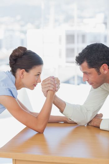 Competitive business people arm wrestling