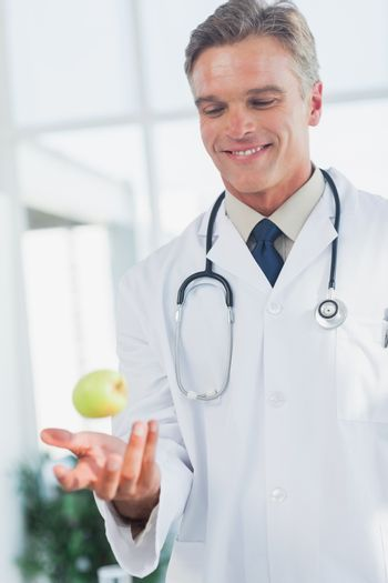 Doctor throwing an apple
