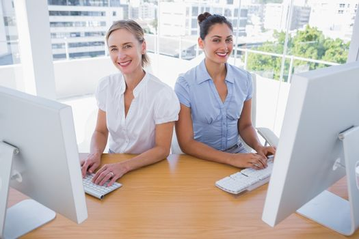 Smiling businesswomen working side by side