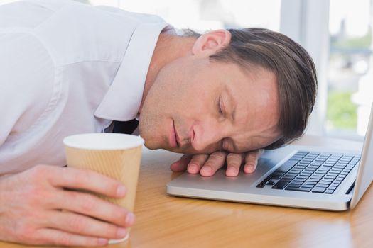 Businessman having a nap on his laptop