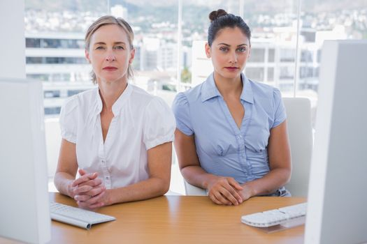 Serious businesswomen sitting side by side